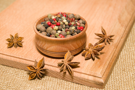 piquancy: A mixture of grains of pepper and star anise on a wooden surface