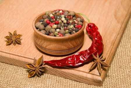 odorous: A mixture of grains of pepper, cilli and star anise on a wooden surface
