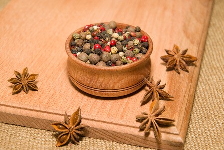 odorous: A mixture of grains of pepper and star anise on a wooden surface