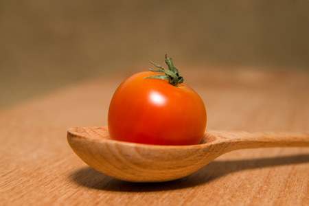 foetus: Ripe red tomatoes in a wooden spoon on a wooden surface Stock Photo