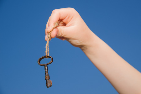 linked hands: Child hand holding an old key on a string against the sky Stock Photo