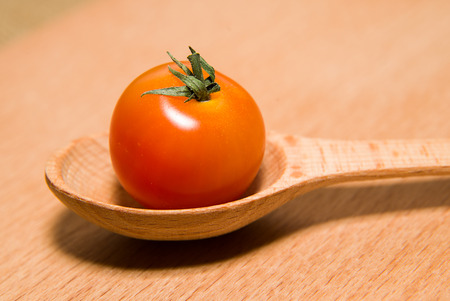foetus: Ripe red tomato in a wooden spoon on a wooden surface