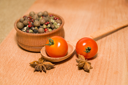foetus: Ripe red tomatoes in a wooden spoon, pepper and star anise on a wooden surface