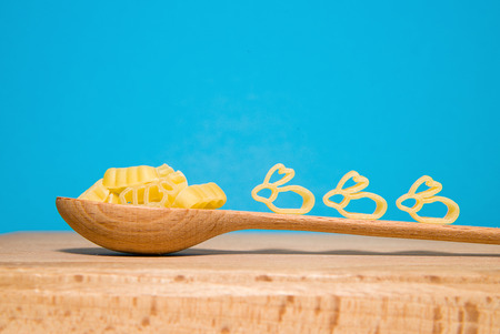 lapin silhouette: Pasta in the form of animals and a wooden spoon on a blue background