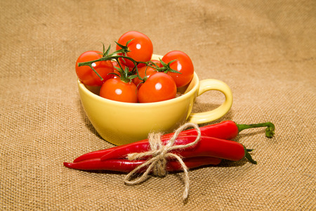 fascicule: Cherry tomatoes in a yellow cup and Chile peppers tied with a rope on old cloth