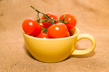 garden stuff: Cherry tomatoes in a yellow cup on old cloth Stock Photo