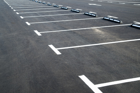 exactness: Markings on asphalt pavement indicating the parking lot in front of the store