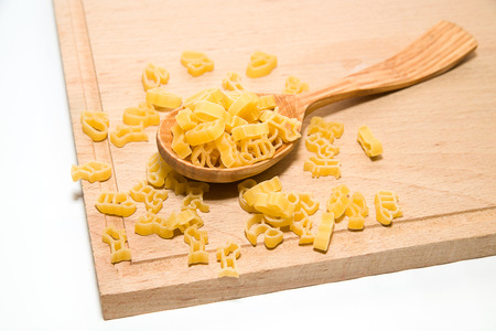 ready to cook food: Pasta in the form of animals and a wooden spoon on a white background