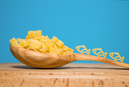 ready to cook food: Pasta in the form of animals and a wooden spoon on a blue background