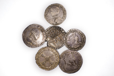 silver coins: A lot of old silver coins with portraits of kings on a white background Stock Photo