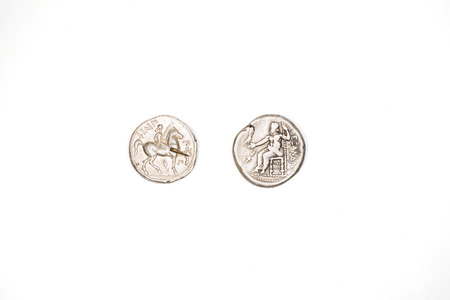 ii: Silver antique coins of Alexander the Great and Philip II on a white background.