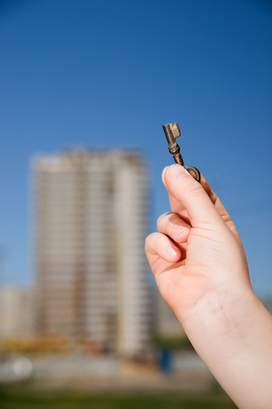 closed fist: Child hand holding an old key  against the sky Stock Photo