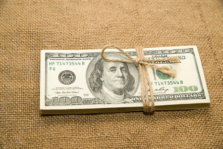 emolument: One pack of dollars tied up with rope in the old cloth Stock Photo