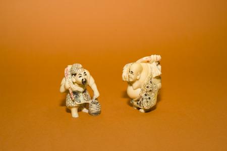 storekeeper: Two vintage figurines Chinese men on a orange background