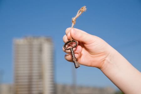 safeness: Child hand holding an old key on a string against the sky Stock Photo