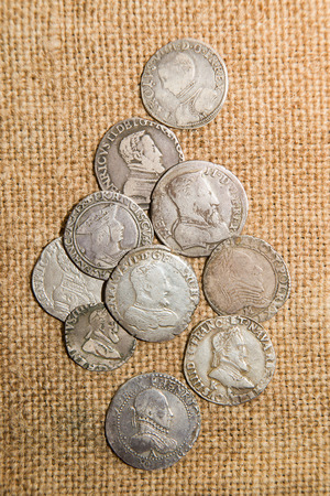 silver coins: A lot of old silver coins with portraits of kings on the old cloth Stock Photo