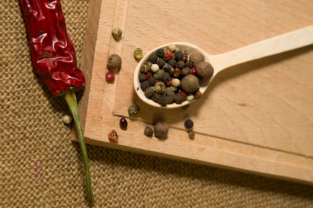 piquancy: Wooden spoon filled with grains of pepper and chilli on a wooden surface