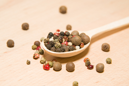 smack: Wooden spoon filled with grains of pepper  on a wooden surface Stock Photo