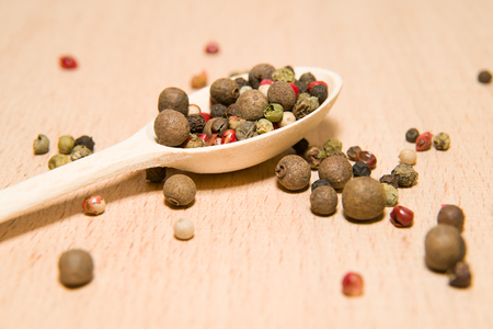 savour: Wooden spoon filled with grains of pepper  on a wooden surface Stock Photo