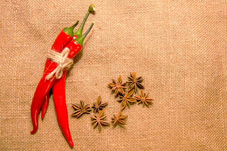 admixture: Three Chile peppers tied with a rope and star anise fruits on old cloth Stock Photo