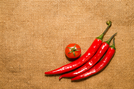 smack: Three Chile peppers and Cherry tomat  on old cloth