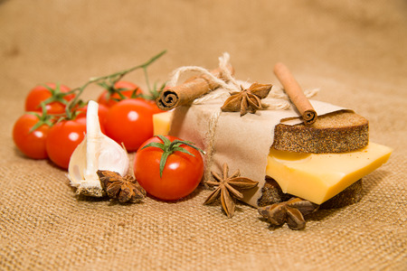 cinnamon stick: Sandwich with cheese wrapped in paper,cinnamon stick,  cherry tomatoes and garlic on old cloth