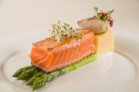 A piece of fried salmon, asparagus, corn porridge on a white plate