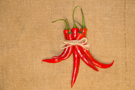 admixture: Five Chile peppers tied with a rope  on old cloth