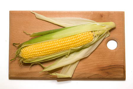 emporium: A ripe fruit of corn on a wooden surface
