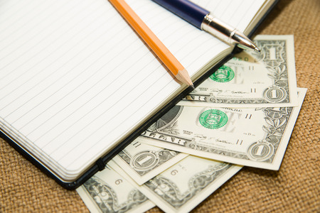 scratchpad: Opened notebook with a blank sheet, pen, pencil and money on the old tissue