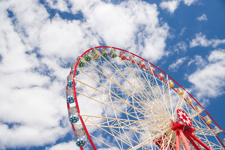 extremity: Atraktsion Ferris wheel against a blue sky with clouds
