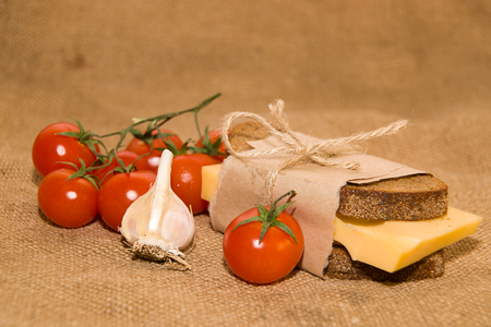 piquancy: Sandwich with cheese wrapped in paper, cherry tomatoes and garlic on cloth