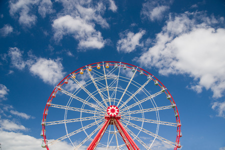 avocation: Atraktsion Ferris wheel against a blue sky with clouds
