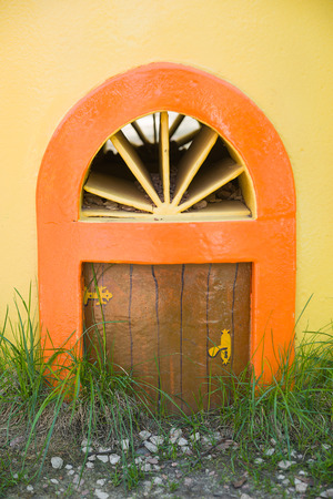meagre: The little door in a yellow wall Stock Photo