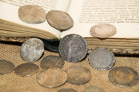 numismatics: A lot of old England  silver coins with portraits of kings on the old cloth Stock Photo