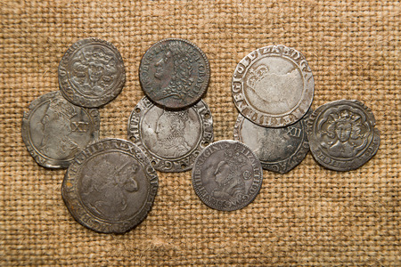 silver coins: A lot of old England  silver coins with portraits of kings on the old cloth Stock Photo