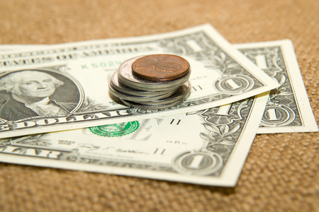 emolument: Dollars banknotes and coins on an old cloth Stock Photo
