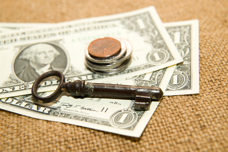 emolument: Dollars banknotes, coins and key on an old cloth
