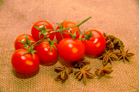 admixture: A lot red Cherry tomatos and star anise fruits on old cloth Stock Photo