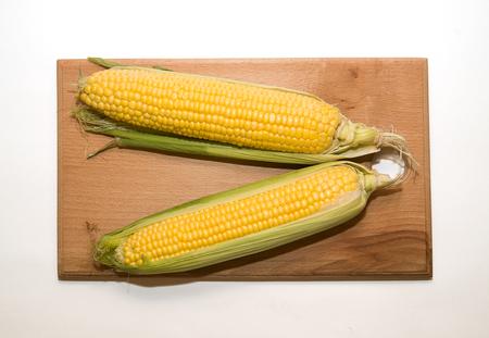 emporium: A few mature ears of corn on a wooden surface