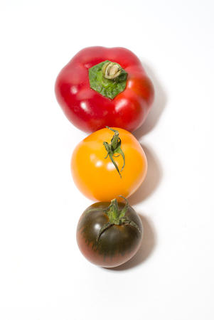 aliments: Two tomatoes and peppers on a white background