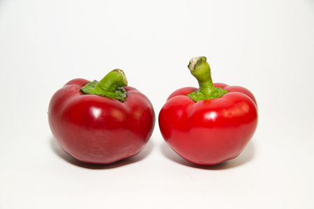 foodstuffs: Two red  peppers on a white background