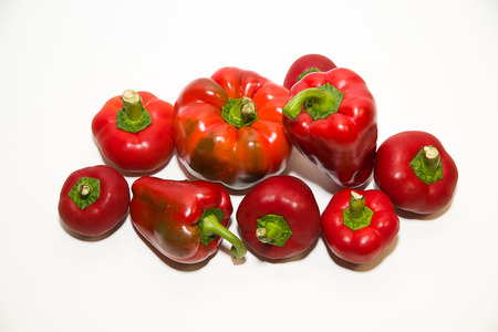 soundness: Many red  peppers on a white background