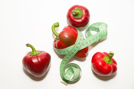 Ripe red peppers and of tailoring meter on over white Stock Photo