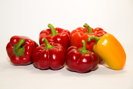 soundness: Many red and yellow  peppers on a white background