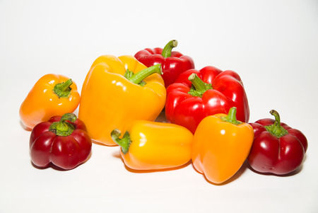 garden stuff: Many red and yellow  peppers on a white background