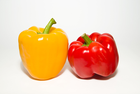 soundness: Two red and yellow  peppers on a white background