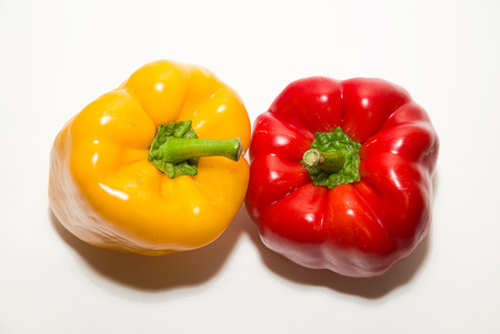 heartiness: Two red and yellow  peppers on a white background