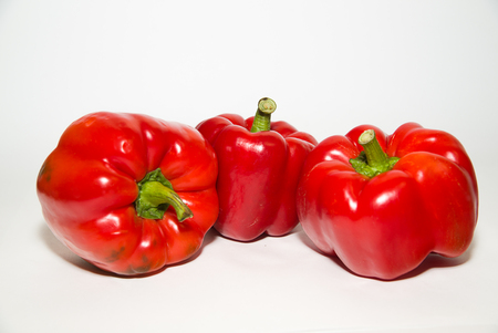 garden stuff: Three red  peppers on a white background Stock Photo
