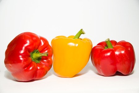 garden stuff: Three red and yellow  peppers on a white background